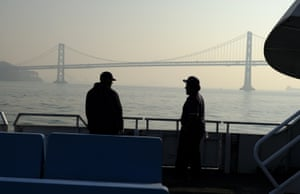 From the deck of a ferry, the San Francisco-Oakland Bay Bridge is obscured.