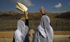 Druze women residing in Majdal Shams in the Israeli-occupied sector of the Golan Heights wave at their Syrian Druze friends and relatives on the other side of the border.