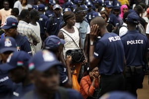 Members of the public and police officers gather outside an office in Banjul where election materials are being distributed.