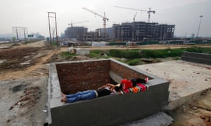 Men rest on a construction site for residential apartments that was halted, unfinished, in 2011.