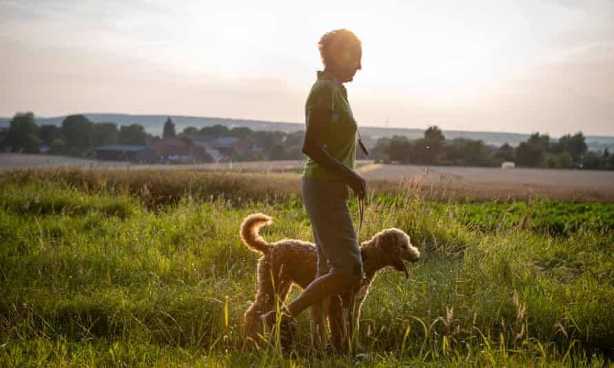 Woman walks with her dog in rural scene