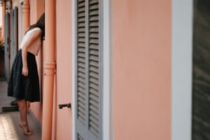 A girl peaks in the window of a pink house