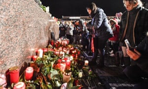People place candles and flowers in the market place for the victims of the shooting in Hanau, Germany, Thursday, Feb. 20, 2020.