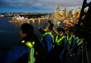 Participants wear glowing vests during a press preview of the Vivid Climb Mandarin for Chinese-language tours of Sydney Harbour Bridge, which includes a boogie on a 70s style flashing dance floor on top of the the structure
