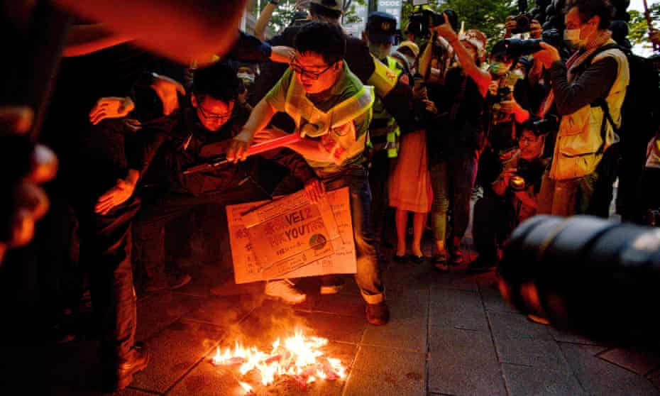 Taiwanese protesters burn a Chinese national flag.