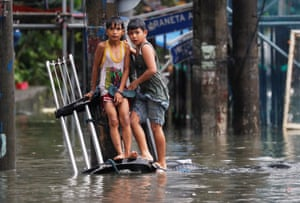 Manila, PhilippinesBoys rest on the partially submerged bumper of a vehicle in flooded Quezon city