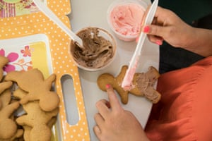 A child paints icing on a gingerbread man, one of the activities for kids while visiting their mothers in prison.