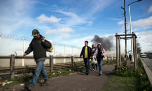 Migrants walk away as the Calais refugee camp is cleared