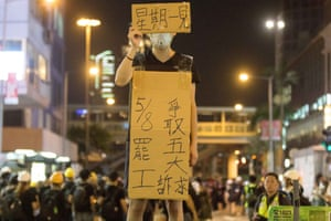 A protester stand with placard asking Hong Kongers to go on strike.