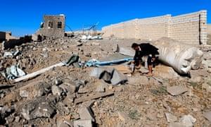 A Yemeni man checks debris of a building destroyed in Saudi-led air strikes in Yemen's capital, Sana'a.