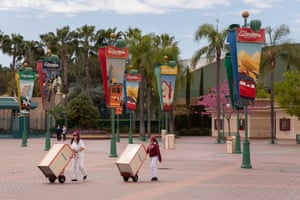 Employees move trashcans at Disneyland while it remains closed due to Coronavirus.