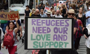 Protests supporting refugees in Australia holding a banner with the words - refugees need our love and support