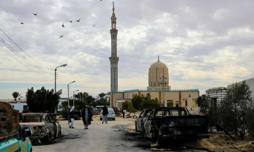 Burnt-out cars line the streets of al-Arish in northern Sinai on Saturday after the terror attack on the mosque.