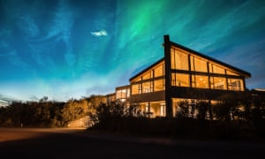The northern lights flicker above Hotel Husafell, Iceland.