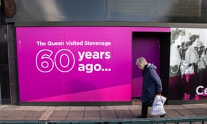 Older person walks in front of hoarding with picture of Queen visiting Stevenage 60 years ago