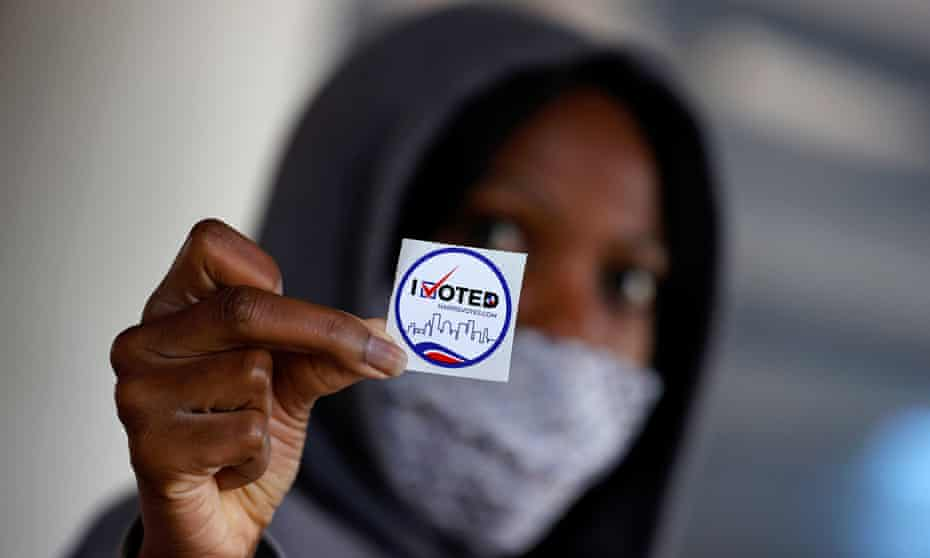 An American woman with a token saying, 'I voted'