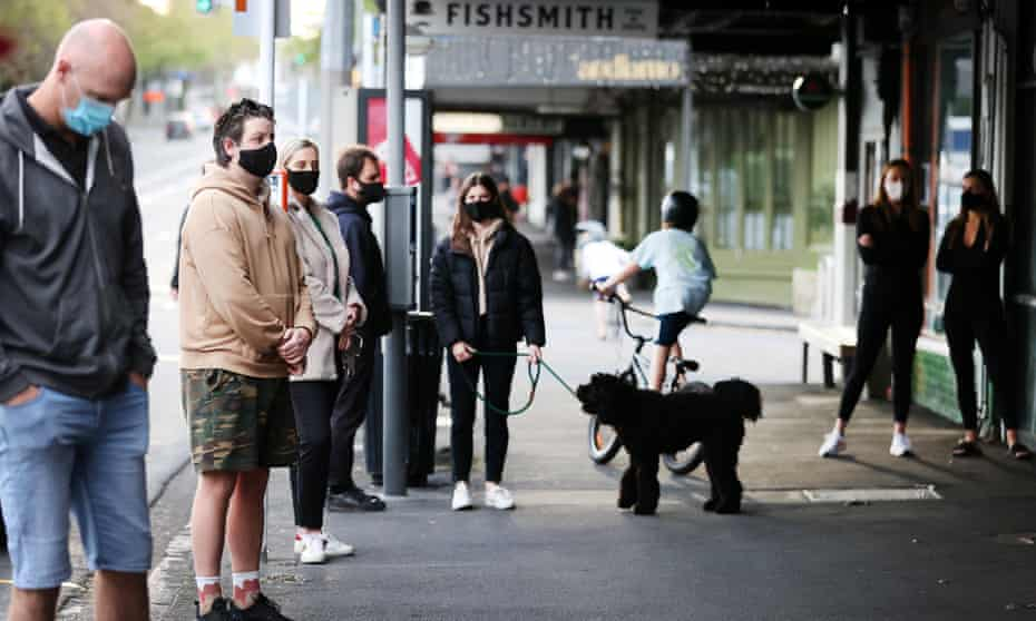 People wait for takeaway coffee outside an eatery in Herne Bay in Auckland, New Zealand