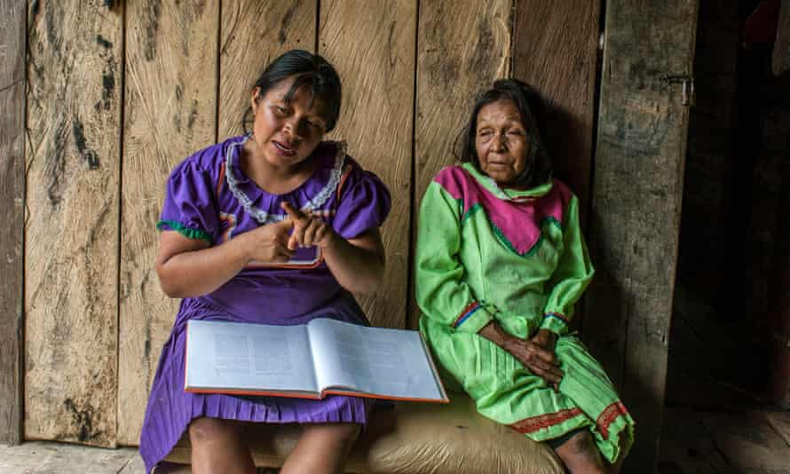 María Noelia Queraguema Nacavera, a midwife apprentice, sits beside her mother Feliciana Nacavera