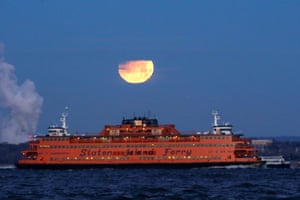 The glowing satellite sets as the Staten Island ferry, in Brooklyn, New York, moves into view