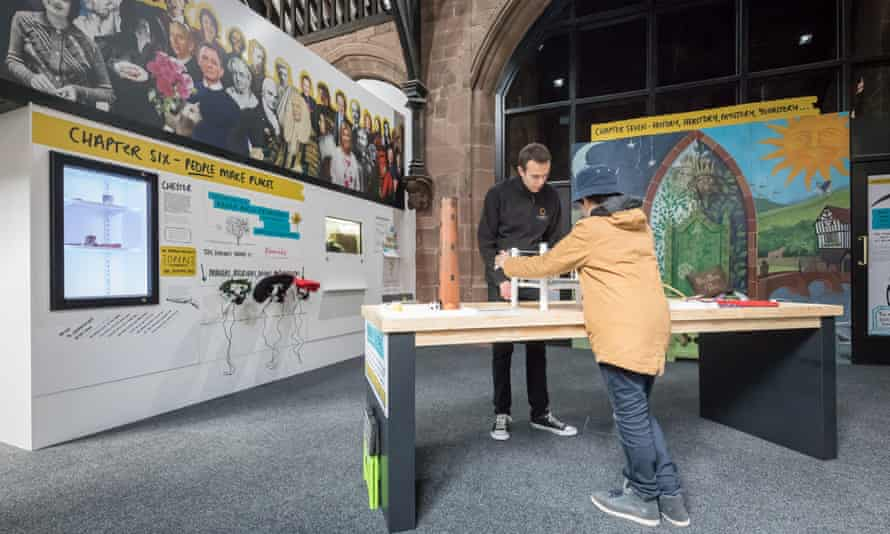 A museum assistant shows a young visitor one of the interactive exhibits at Chester: A Life Story museum.