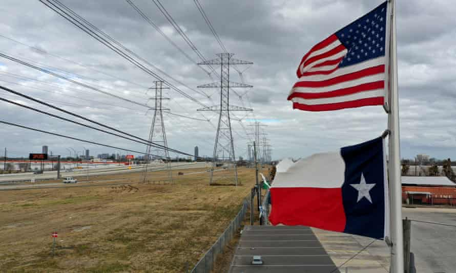 The US and Texas flags fly in front of high voltage transmission towers in Houston, Texas, on Sunday.