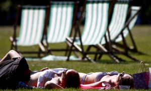 People relax in the sunshine in St James's park in London.