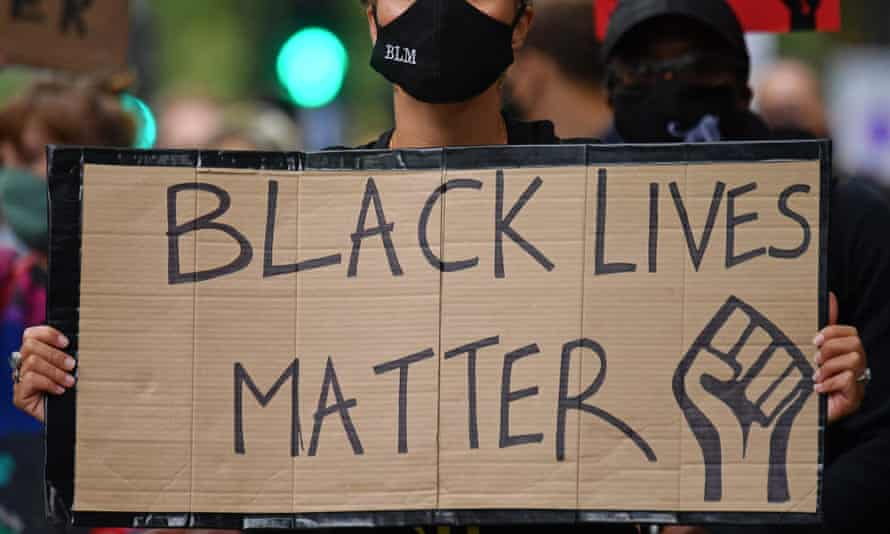 A protester holds up a placard in support of the Black Lives Matter movement during the inaugural Million People March march from Notting Hill to Hyde Park in London in August 2020.