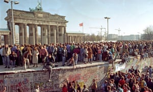 Crowds climb the Berlin Wall in 1989