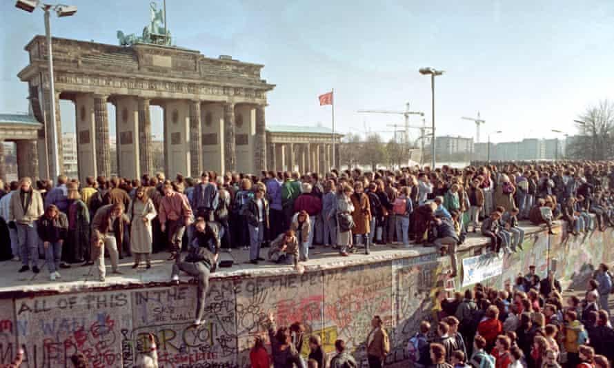 Crowds climb the Berlin Wall in 1989