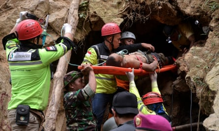 Indonesian rescuers evacuate a survivor from the collapsed illegal gold mine in Bolaang Mongondow, North Sulawesi