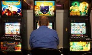 A man plays a poker machine in a Sydney club