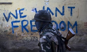An Indian paramilitary soldier walks past graffiti on a wall in Srinagar, Indian-controlled Kashmir