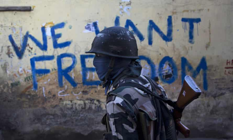 An Indian paramilitary soldier walks past graffiti on a wall in Srinagar, Indian-controlled Kashmir