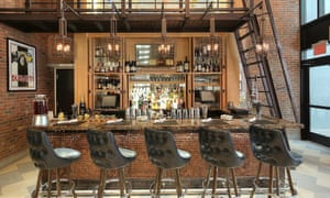 The Bugatti bar at the Archer hotel in New York City. Chairs are lined up in front of the bar, while around the exposed brick walls there are Bugatti posters.
