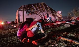 Henry Ramirez and his mother Maribel Morales survey severe damage to their church after a tornado tore through North Dallas Sunday.