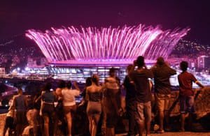 People watch fireworks explode over the stadium, from the Mangueira favela.