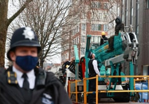 A police officer talks to a protester who has climbed on a crane