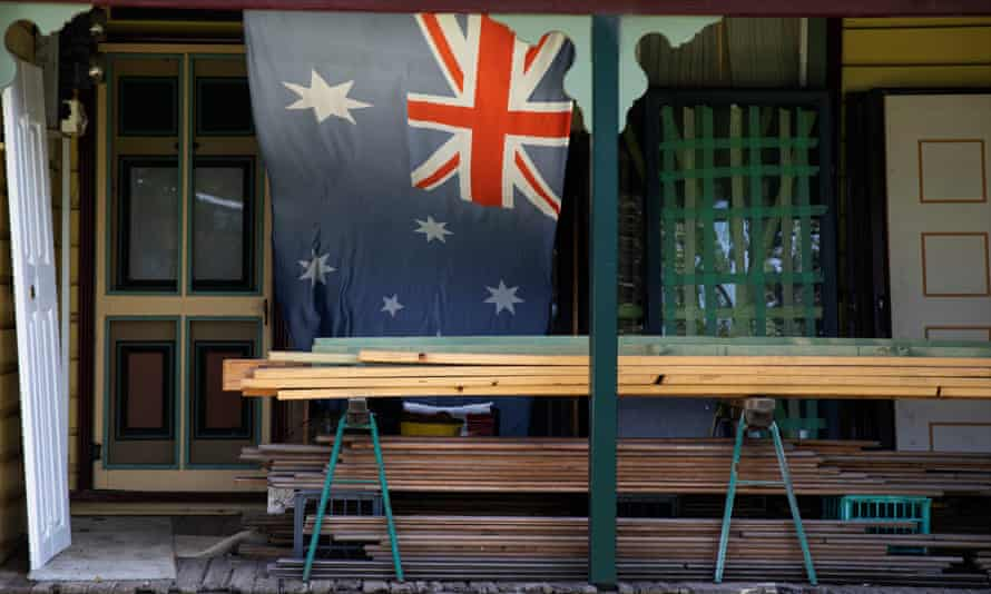 An Australian flag hangs on the front of a cottage in Muswellbrook.