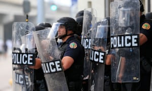 Police in riot gear use tear gas as they blockade the station's parking garage as a rally in response to the police killing George Floyd on 30 May 2020 in Miami, Florida.