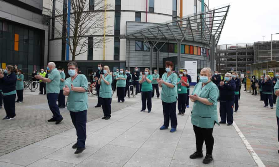 People clap after observing a minute's silence outside the Queen Elizabeth university hospital in Glasgow