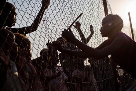 At the UN camp in Malakal, a girl hits children through a fence that divides the Nuer and Shiluk ethnic groups