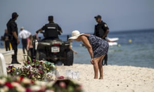 A tourist reads messages left at a makeshift memorial at the beach near the Imperial Marhaba resort.