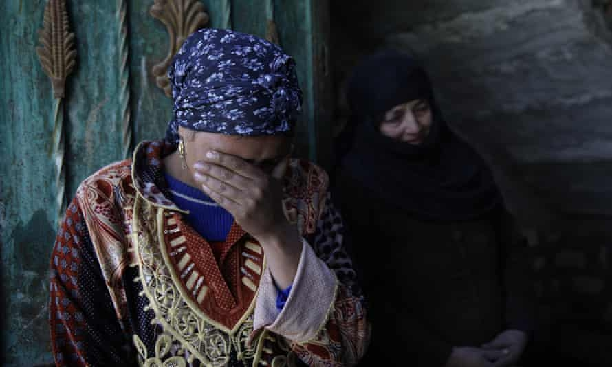 Relatives of abducted Coptic Christian Samuel Walham, weep outside their home in the village of el-Aour, south of Cairo