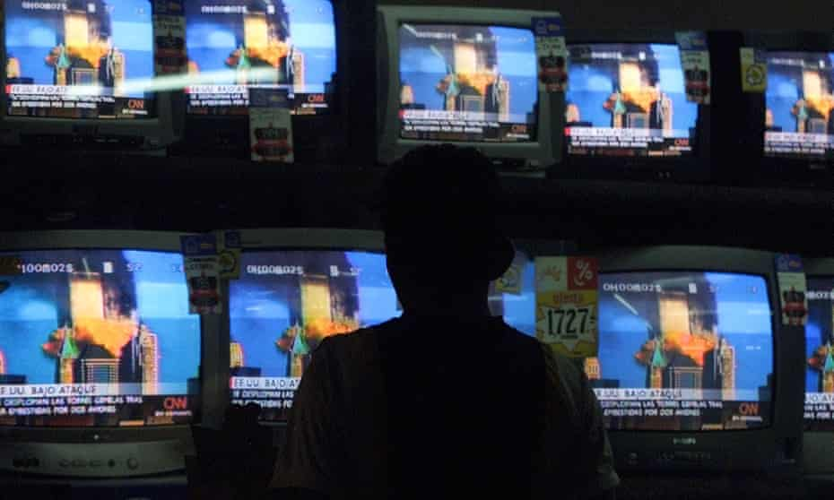 A man in Guatemala watches the destruction of the World Trade Center live on television.