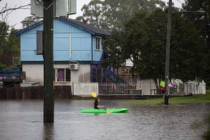 A child paddles a canoe along Church Street in Windsor