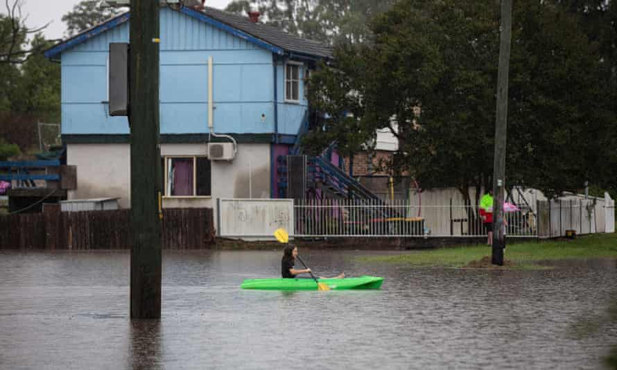 A child paddles a canoe in a flooded street in Windsor, NSW, on Monday morning
