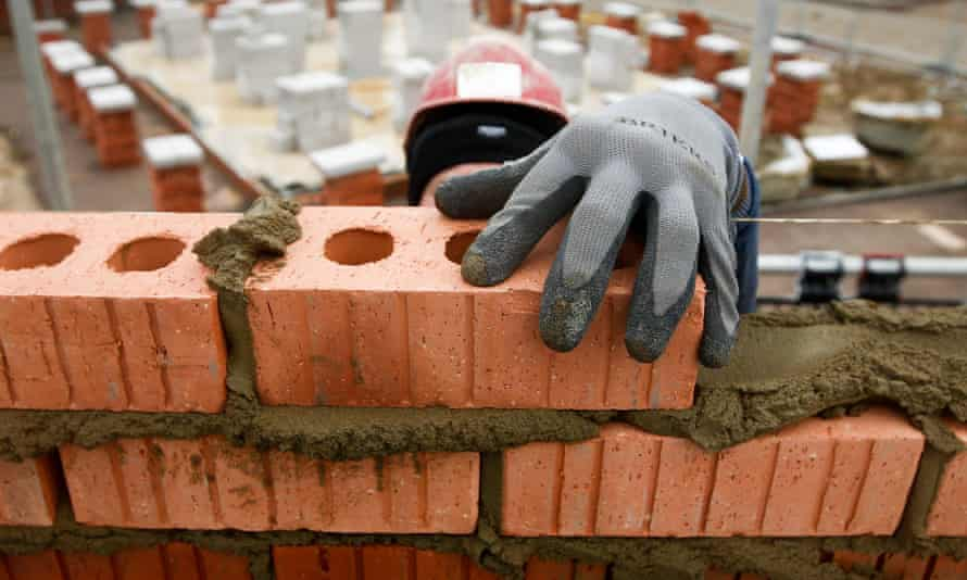 A construction worker lays bricks