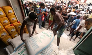 Workers unload sacks at aid distribution centre