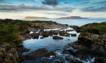 A waterfall flows along a small gorge to form a still pool with almost infinity aspect out to sea, looking out eastward to the isle of Eigg.