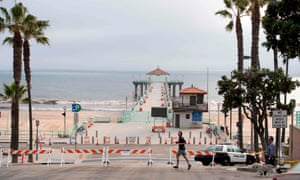 People walk by the closed pier, beach and strand in Manhattan Beach, California, on 28 April.